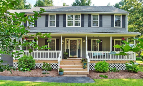 Colonial style home - gray with farmer's porch out front, white trim, black shutters, young plantings out front and flower pots on the steps leading to the entrance.