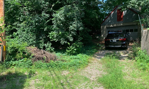 Wooded lot with fence shown on the right side, a pole on the left and a vehicle in front of a garage in the rear.