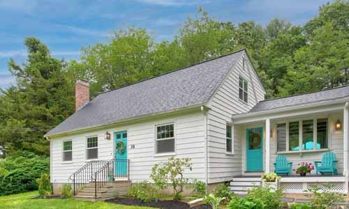 Detached White Cape with two bright blue teal doors and two adirondack chairs of the same color on the front porch; surrounded by trees in the back and pretty plantings out front.