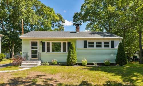 Detached light green ranch with white trim surrounded by trees.