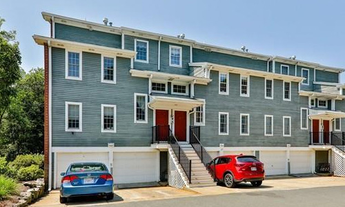 exterior of multi-level townhouse property shown - blueish gray with white trim, stairs leading up to two red doors and six garage doors