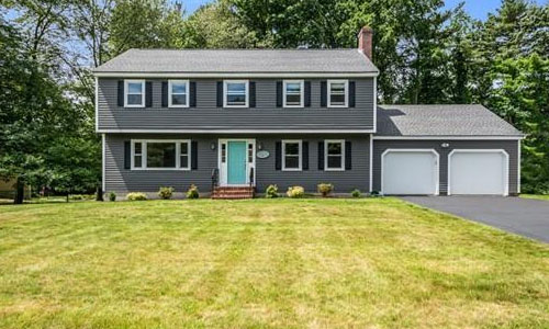 Detached Gray Colonial, Garrison for sale - exterior of home shown - dark gray with white trim and blue door