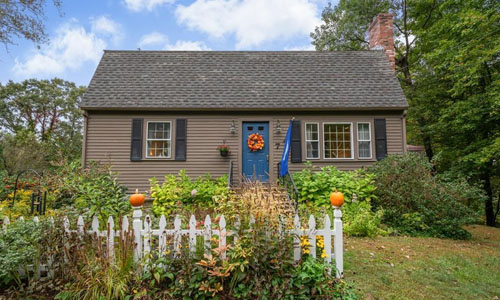Detached Brown Cape for sale - exterior of home shown - tan with black shutters, blue door, white fence and fall decorations