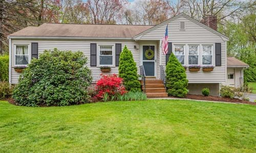 Three bedroom ranch in Westborough MA - tan with green door and black shutters, stone steps with rod iron rails and large shrubs out front
