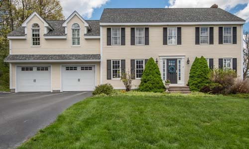Four bedroom colonial home in Shrewsbury MA - tan with white trim, two white garage doors, dark door and shutters, stone steps and large shrubs out front