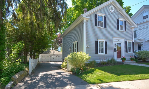 Three bedroom colonial in Westborough MA - light gray with red door and black shutters, stone step and walkway with potted plants and shrubs out front
