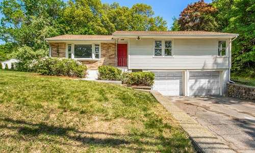 Three bedroom ranch style home in Worcester MA - white with partial brick front, white trim, red door, two white garage doors