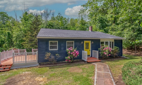 Dark blue ranch style home with white trim, yellow door, brick walkway and fenced in deck on the left side