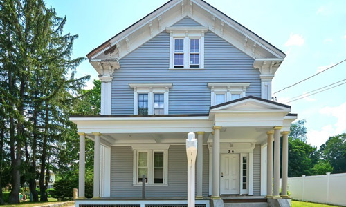 gray two family home with white trim, no shutters, white door, covered entrance and porch out front