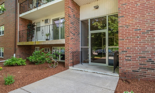 Exterior of brick building with multiple condominium units, glass doors, balconies and rod iron railings with plantings out front.