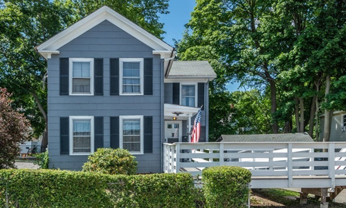 Blue Colonial style home with white trim, black shutters, covered entranceway with white door, an American flag, and a white fenced in deck shown to the right