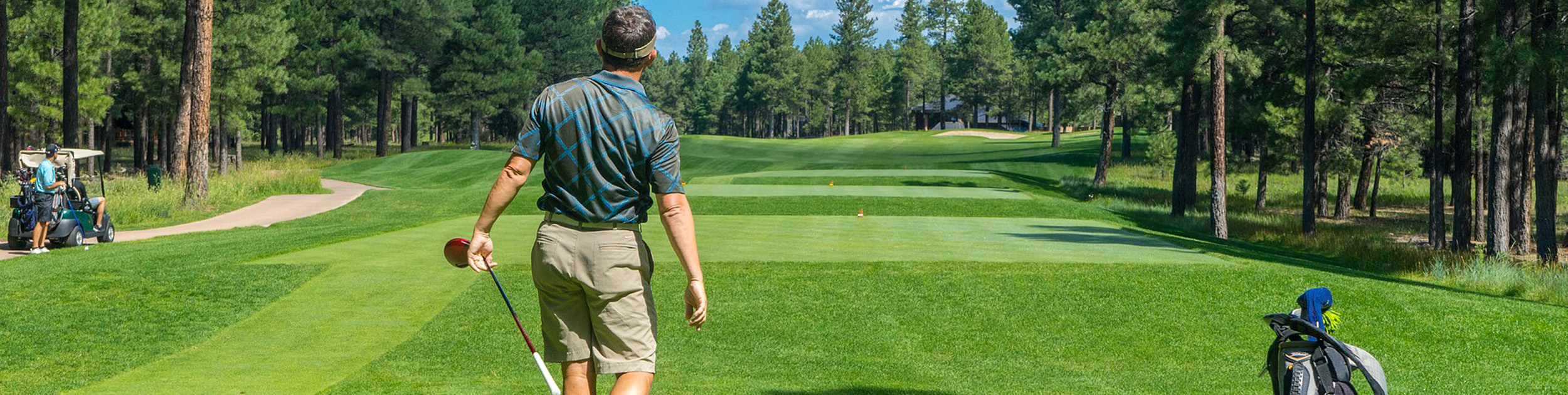 man gazing down golf course after making a swing
