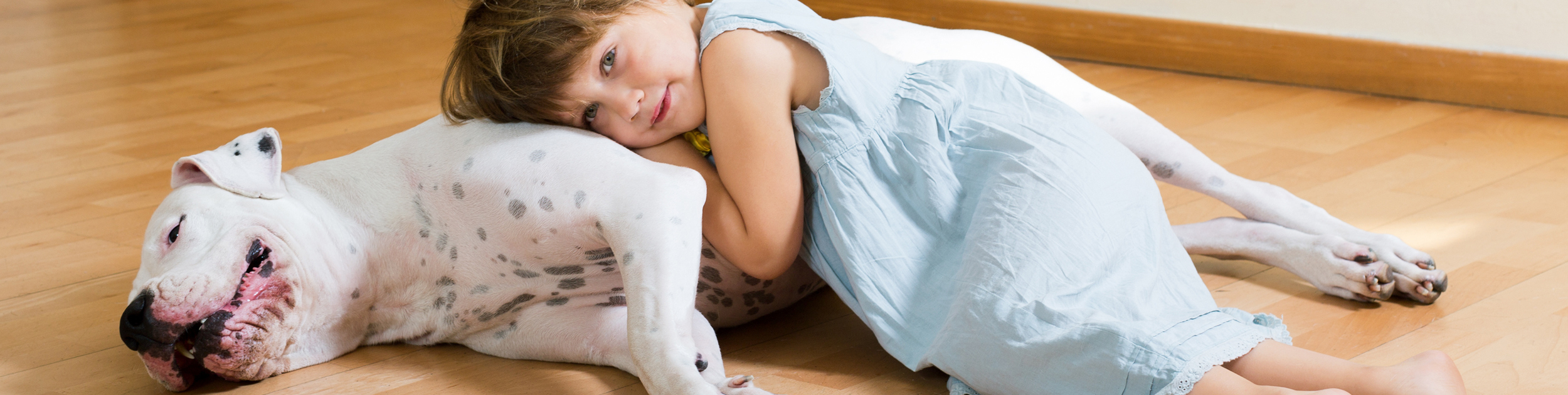 little girl laying on hard wood floor with dog