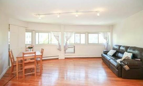 two bedroom condo for rent in Cambridge, MA - open area of living room and eat-in area shown with gleaming hardwood flooring