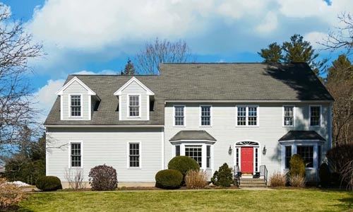 Light gray Colonial style home for sale in Natick, MA - home has white trim, a red door and two bow windows on front