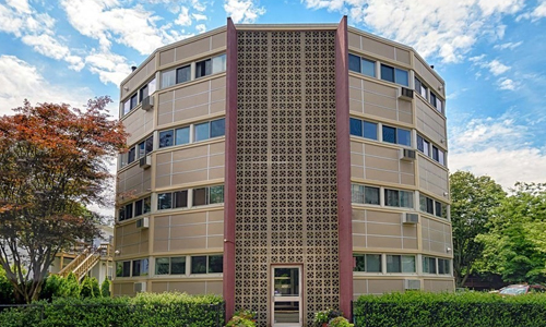 Multi unit condominium building - round in shape, four floors high, dark tan with lots of windows and a full height decorative section surrounding the entrance out front