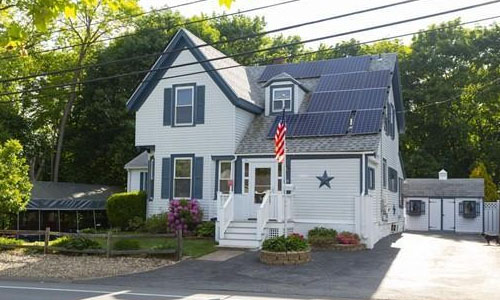 exterior image of two family home for sale - white with blue trim, a star on the front and a flag pole
