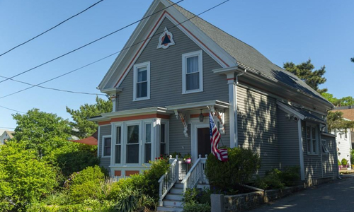Three bedroom colonial for sale in Gloucester MA - exterior of building shown, gray with American flag in front