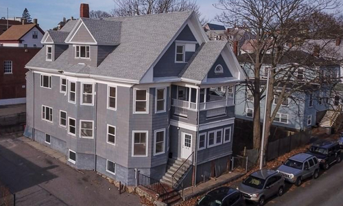 Two bedroom garden style condo for sale in Gloucester MA - exterior of multi-level gray building with lots of peaks, white trim and front porches shown