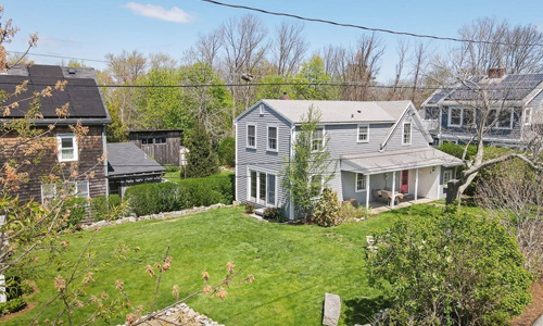 Three bedroom Colonial style home in Gloucester MA - exterior of property shown - light gray with covered porch out front, a red door and a large lawn out front and to the left side of the house
