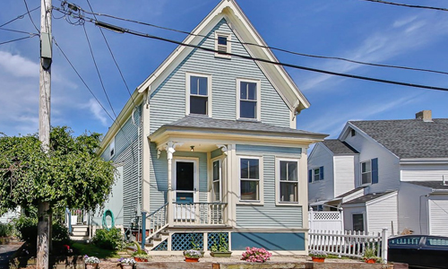 Light green colonial style home in Gloucester MA - exterior of property shown - white trim, enclosed porch on first floor and peaked roofline.