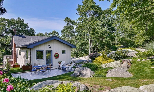 Side view of a beige cottage with blue trim on the peaked roofline in Gloucester MA - there is a patio with multiple seating options and the home is surrounded by beautiful landscape.