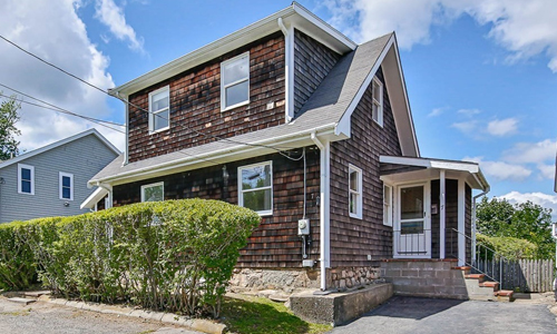 Brown shingled colonial style home in Gloucester MA with hedges out front and side covered porch entrance.