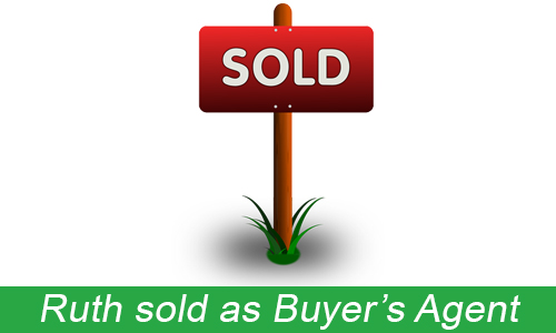 red and white sold sign on stick in grass