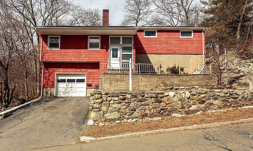 Red split entry style home with white door and garage door surrounded by bare trees and a stone wall out front