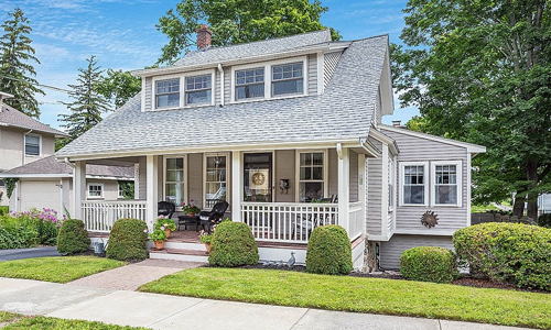 Light gray colonial style home with white trim, farmer's porch, well maintained hedges and flower pots out front - surrounded by bare trees and a blue sky